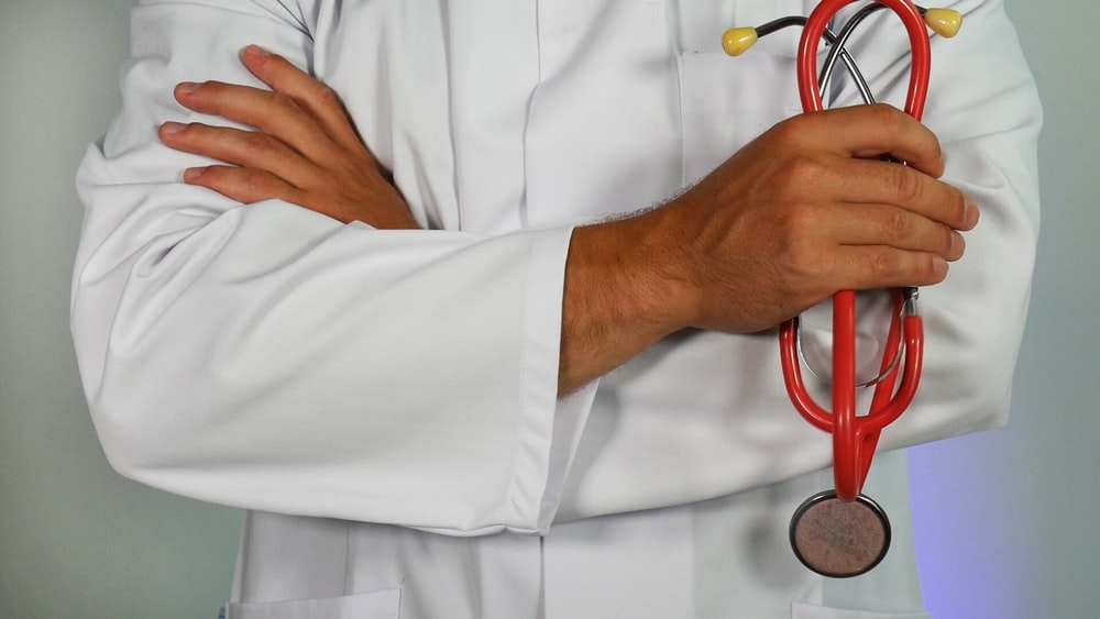 octor holding red stethoscope