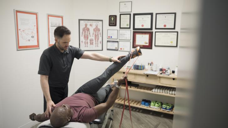 African American male patient in physical therapy using stretch band on leg