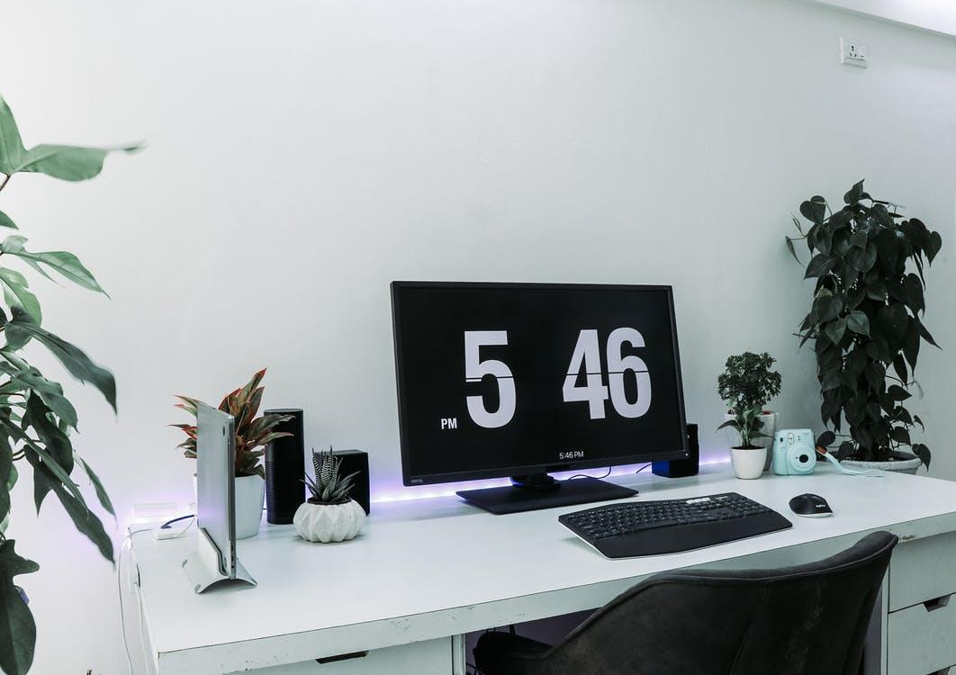 Black Flat Screen Computer Monitor and Black Computer Keyboard on Top of White Table