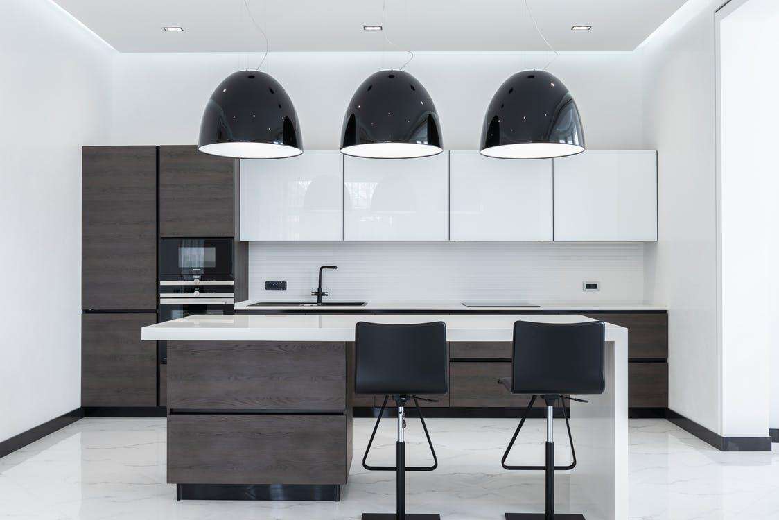 Creative lamps hanging over table with chairs in spacious kitchen with modern furniture and appliances