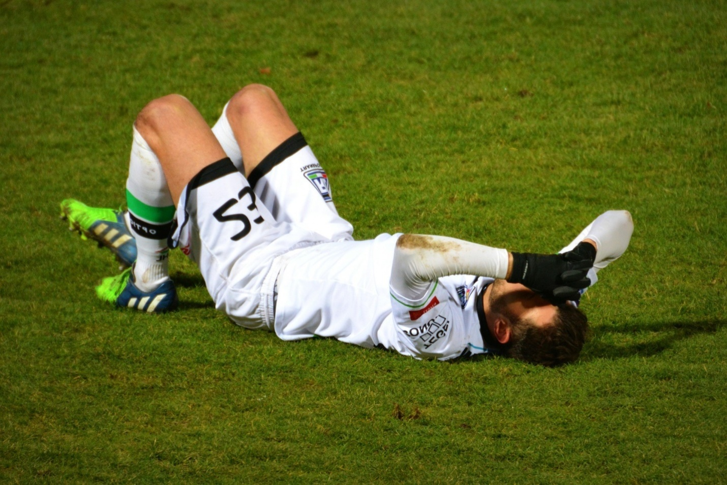 A football player falling on the ground  Description automatically generated with low confidence