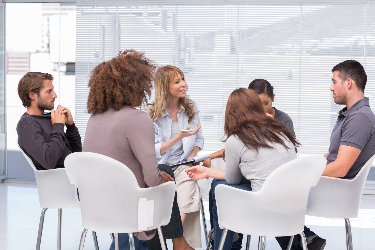 A group of people sitting in chairs Description automatically generated with medium confidence