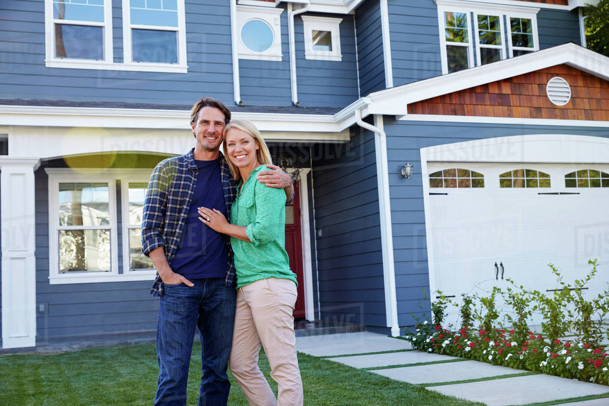 Portrait Of Couple Standing Outside House - Stock Photo - Dissolve